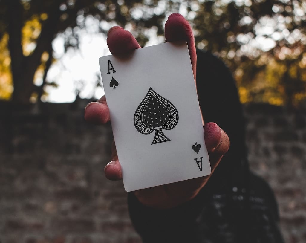 hooded magician holding up ace playing card