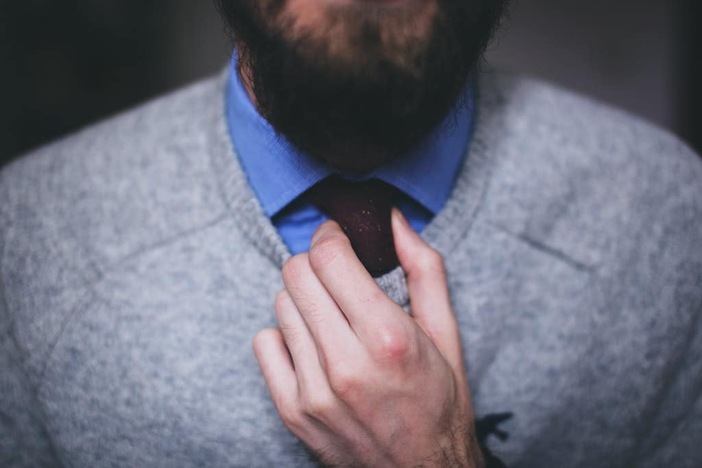 man adjusting tie knot to dress for success as he learns leadership qualities
