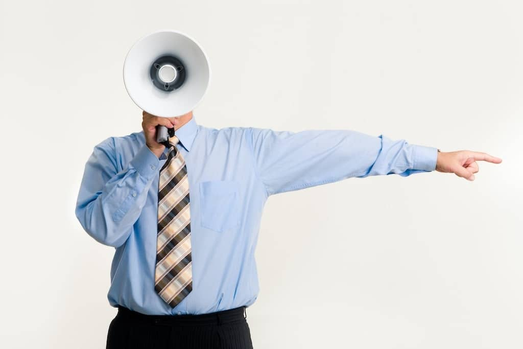 man in business clothes yelling through a megaphone while pointing to display poor leadership skills by poor communication skills